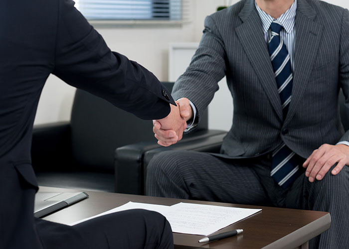 握手を交わすスーツ姿の男性