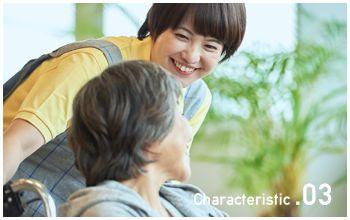 車椅子の女性に微笑みかけるスタッフ